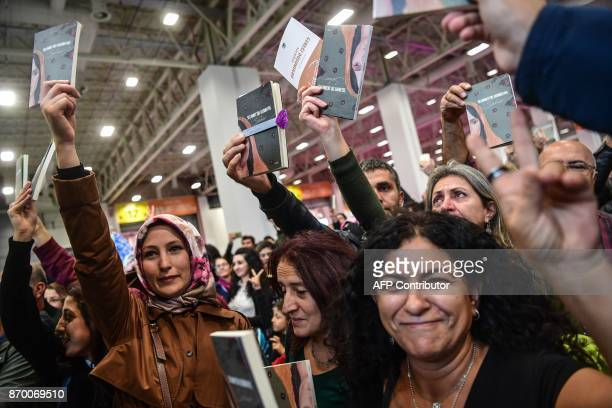 People hold the detained leader of Pro Kurdish Peoples Democratic Party Selahattin Demirtas' book 'Seher' during a symbolic book signing on November...