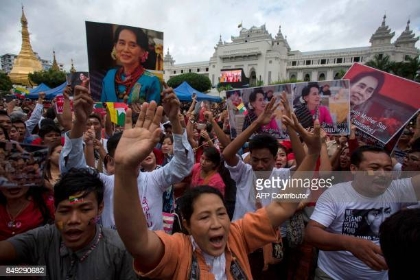 TOPSHOT People hold the Myanmar national flag and placards as they attend a public gathering to listen to the live speech of Myanmar's State...