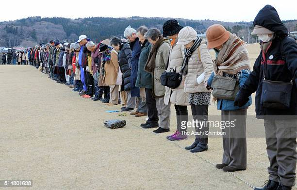 People hold their hands observe a minute of silence at 246pm when the magnitude 90 earthquake struck five years ago at Tanesashi Beach on the fifth...