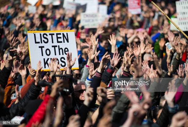 People hold their hands up as directed by musician Brandi Carlile at Seattle Center during the March for Our Lives rally on March 24 2018 in Seattle...
