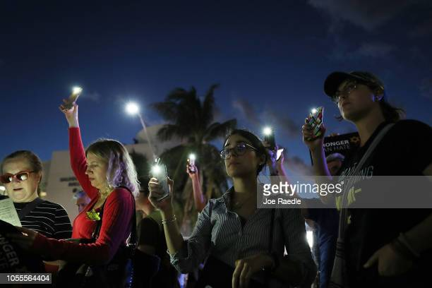 People hold their phones with the flashlight on up in the air as they gather together for a CommunityWide Solidarity Vigil at the Holocaust Memorial...
