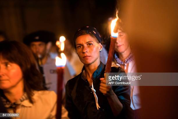 """People hold torches as they walk along """"August 31"""" street in the northern Spanish Basque city of San Sebastian on August 31 during the commemoration..."""