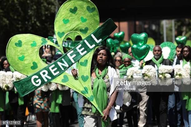 People hold tributes as they walk to the Wall of Truth to mark the one year anniversary of the Grenfell Tower fire on June 14 2018 in London England...