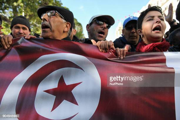 People hold Tunisian flag as they chant slogans during the celebration of the 7th anniversary of the Tunisian revolution the sevenyear anniversary of...