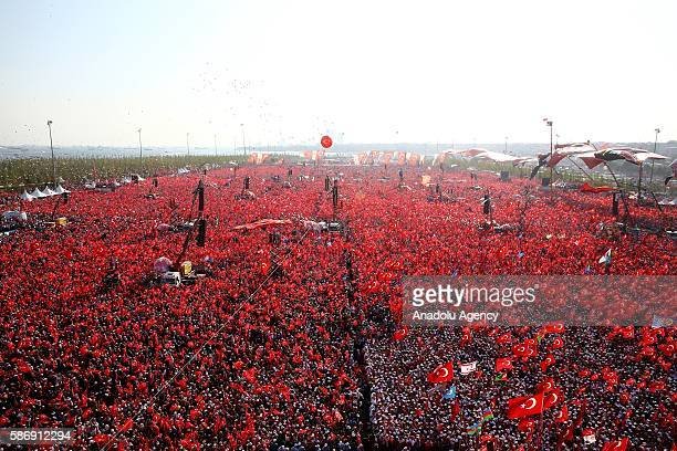 People hold Turkish flags as they take part in Democracy and Martyrs' Rally held to protest against the July 15 failed coup by the Fetullah Terrorist...