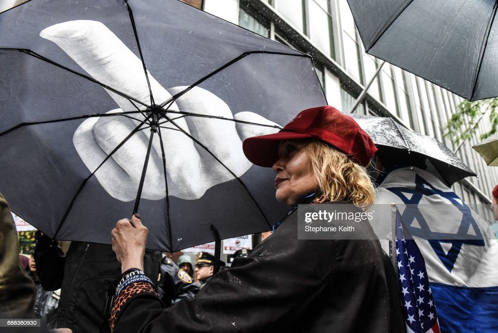 People hold umbrellas and flags as part of an Alt Right protest of Muslim Activist Linda Sarsour on April 25, 2017 in New York City.