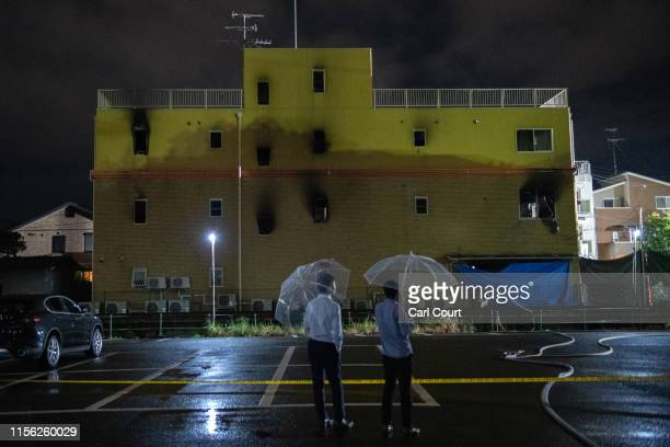People hold umbrellas as they pause next to the Kyoto Animation Co studio building after it was set ablaze by an arsonist on July 18, 2019 in Kyoto,...