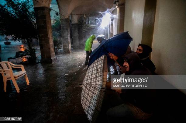 TOPSHOT People hold umbrellas as they protect themselves from heavy rain in Monterosso al Mare village in the Liguria region on October 29 2018 Ahead...