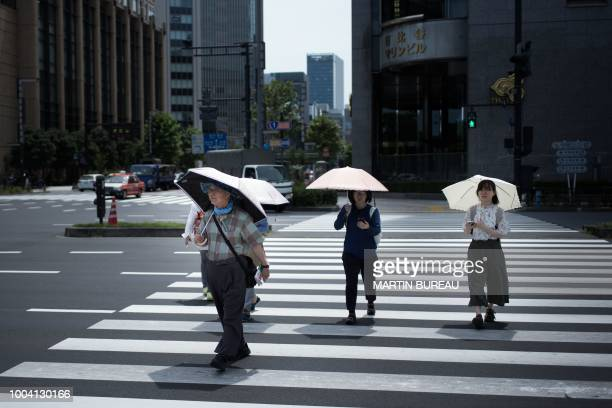 People hold umbrellas as they walk along a street in Tokyo on July 23 as Japan suffers from a heatwave Japan's severe heatwave killed at least 15...