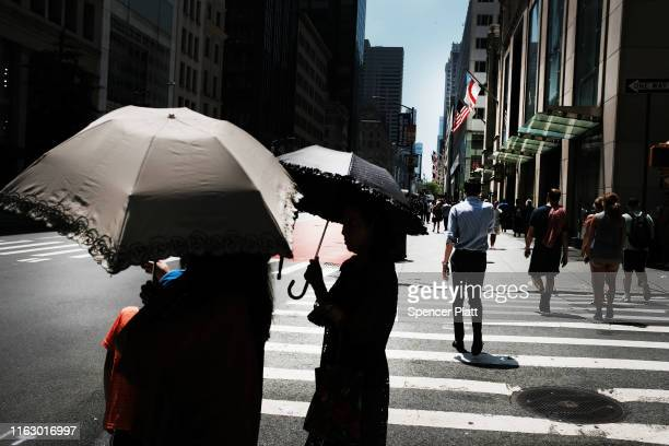 People hold umbrellas during the start of heat wave across the US on July 19 2019 in New York City Much of the East Coast is experiencing abnormally...