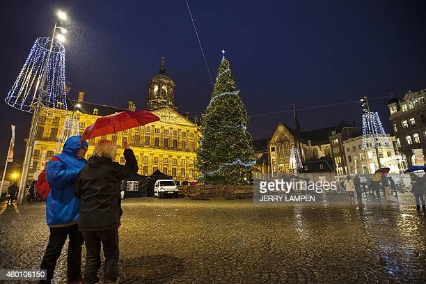 People hold umbrellas under the rain during the lighting of the Christmas tree on Dam Square in Amsterdam the Netherlands on December 7 2014 OUT