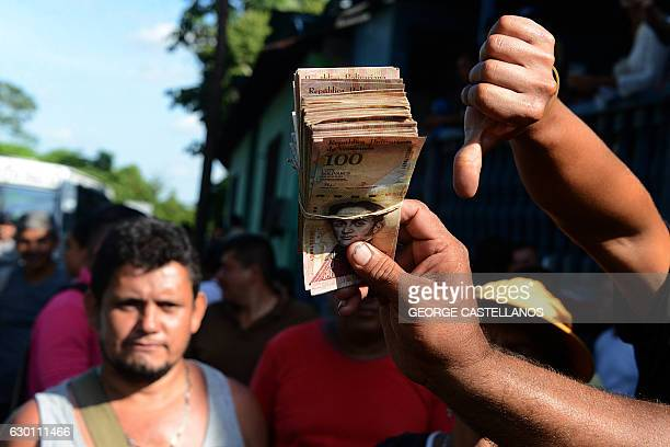 People hold up 100Bolivar notes during a protest over lack of cash as the new bank notes have not yet appeared at the 'Troncal 5' road in San...