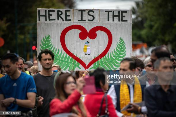 People hold up a banner as they take part in a march to remember victims of the Christchurch mosque attacks, on March 23, 2019 in Christchurch, New...