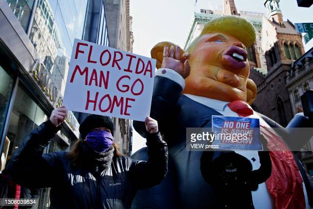 People hold up a placard during a protest against the former U.S. President Donald Trump at Trump Tower on March 08, 2021 in New York. Trump is...