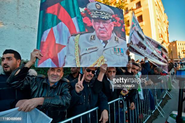 People hold up a portrait of Algeria's late military chief Lieutenant general Ahmed Gaid Salah as they gather outside the Palais du Peuple during his...