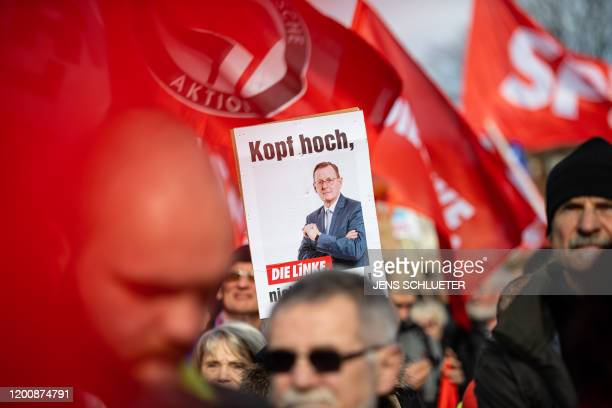 People hold up a poster depicting Thuringia's former state premier Bodo Ramelow of the leftwing Die Linke party and reading Keep the head up during a...