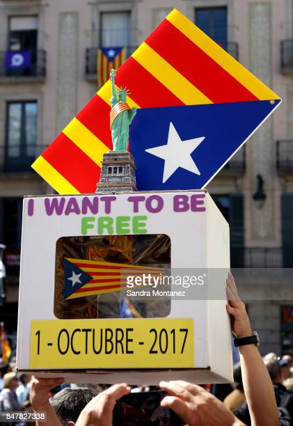 People hold up a replica of a ballot box with a Statue of Liberty with a Catalan flag ribbon next to a Catalan ProIndependece flag during a...