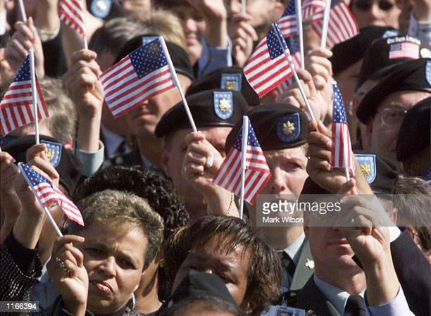 People hold up American flags during a Memorial Service at the Pentagon October 11 2001 in Arlington VA