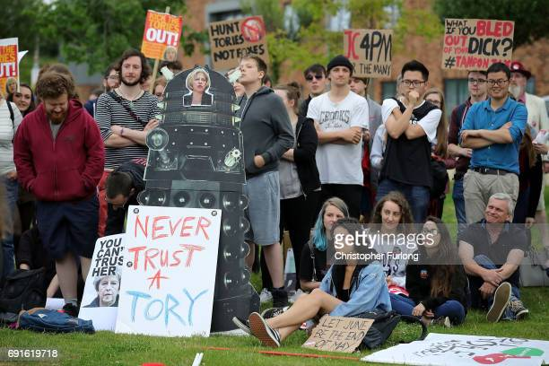 People hold up antiTory protest signs as they wait for British Prime Minister Theresa May and Leader of the Labour Party Jeremy Corbyn to arrive at...