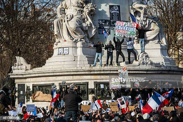 People hold up banners as demonstrators make their way along Place de la Republique during a mass unity rally following the recent terrorist attacks...