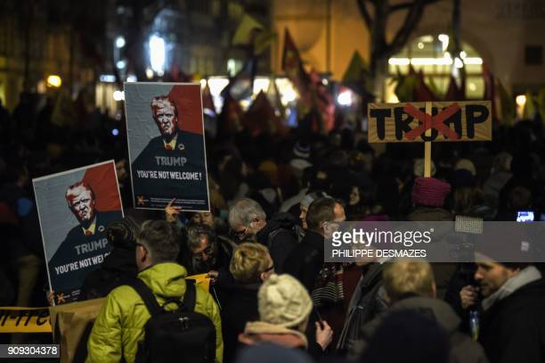 People hold up banners with the image of the US president as they protest against his attendance to the upcoming Davos World Economic Forum on...