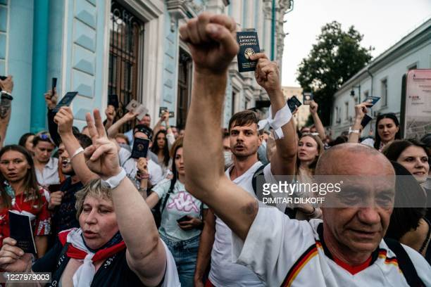 People hold up Belarusian passports as they protest outside the Belarusian embassy after polls closed in Belarus' presidential election, in Moscow on...