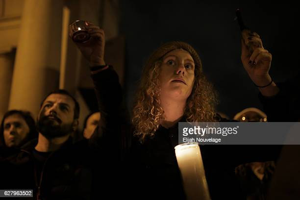 People hold up candles and burning wood during a vigil for the victims of a warehouse fire that has claimed the lives of at least thirtysix people on...