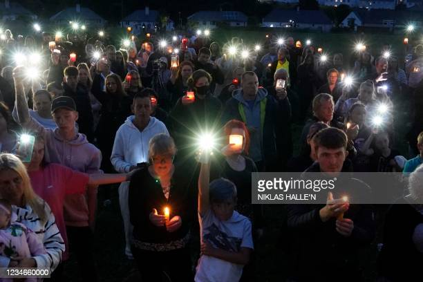 People hold up candles and mobile phone torches during a vigil in North Down Crescent Park in the Keyham area of Plymouth, southwest England, on...