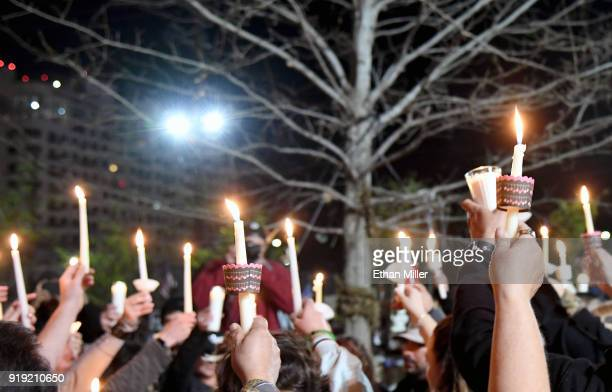 People hold up candles during a vigil put together by the Route 91 Foundation at the Las Vegas Community Healing Garden for victims of Wednesday's...