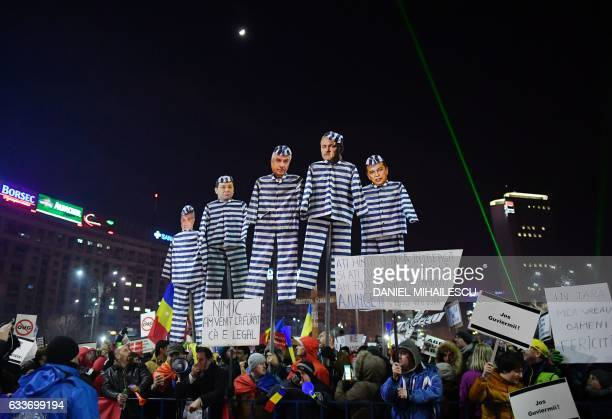 People hold up cardboard cut-outs of figures from the Social Democratic Party rulling party during a protest in front of the government headquarters...