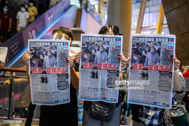 People hold up copies of the Apple Daily as they protest for press freedom inside a mall in Hong Kong on August 11 a day after authorities conducted...