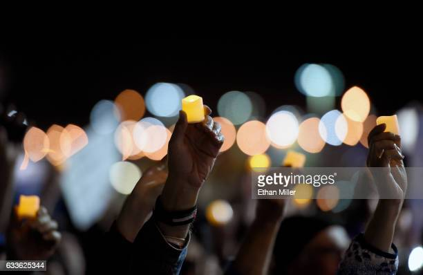 People hold up electric candles as they attend a vigil outside Nevada Republican Sen Dean Heller's office on February 2 2017 in Las Vegas Nevada The...
