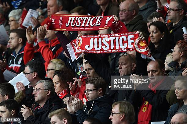 People hold up football scarves during a memorial service at Anfield in Liverpool north west England on April 15 on the 27th anniversary of the...