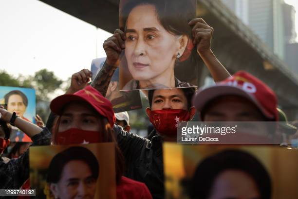 People hold up images of Myanmar's de-facto leader Aung San Suu Kyi at a protest outside Maynmar's embassy on February 01, 2021 in Bangkok, Thailand....