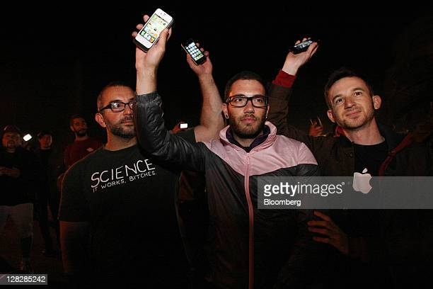 From left to right Adam Palazzo AJ Maiorano and Michael Pieracci hold up iPhones during an iPhone vigil for Steve Jobs cofounder and former chief...