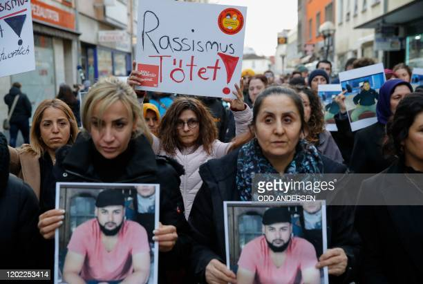 People hold up photos of some of the victims and a placard that reads Racisim Kills during a march following a vigal outside a shisha cafe in Hanau...