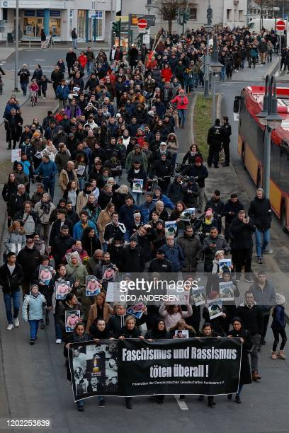 People hold up photos of some of the victims during a march following a vigal outside a shisha cafe in Hanau near Frankfurt am Main, western Germany...