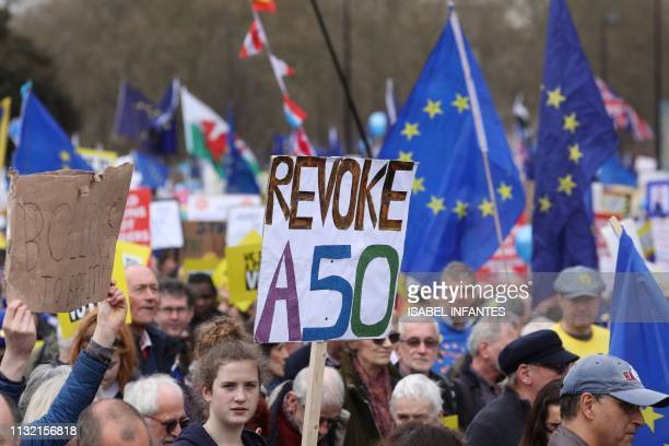 People hold up placards and European flags as they attend a march and rally organised by the proEuropean People's Vote campaign for a second...