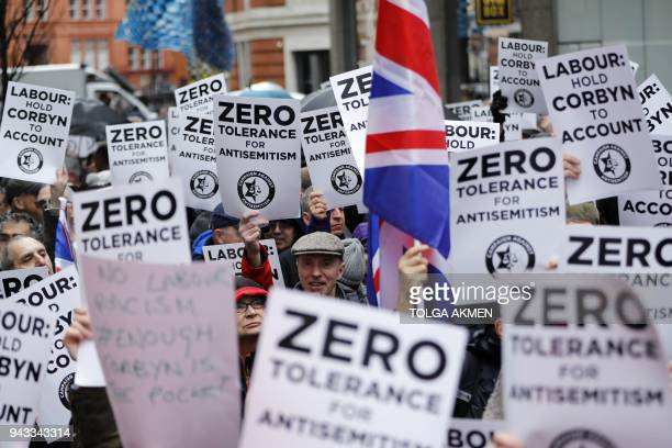 TOPSHOT People hold up placards and Union flags as they gather for a demonstration organised by the Campaign Against AntiSemitism outside the head...