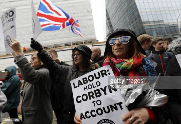 People hold up placards and Union flags as they gather for a demonstration organised by the Campaign Against AntiSemitism outside the head office of...