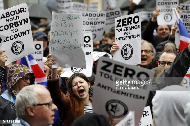People hold up placards as they gather for a demonstration organised by the Campaign Against AntiSemitism outside the head office of the British...