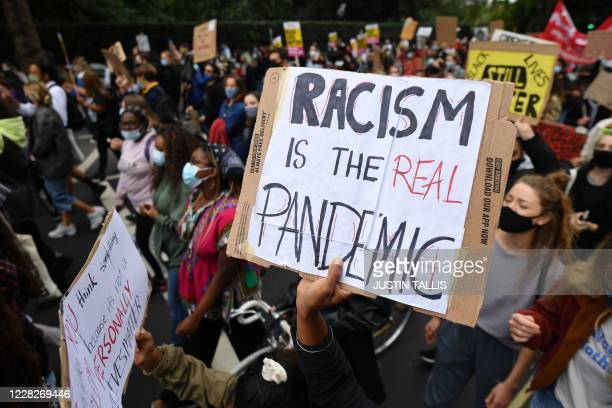People hold up placards as they take part in the inaugural Million People March march from Notting Hill to Hyde Park in London on August 30 to put...