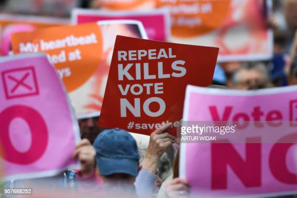 TOPSHOT People hold up placards during a 'Stand up for Life' rally calling for a 'no' vote in the upcoming referendum to preserve the eighth...