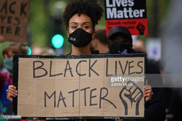 People hold up placards in support of the Black Lives Matter movement as they take part in the inaugural Million People March march from Notting Hill...