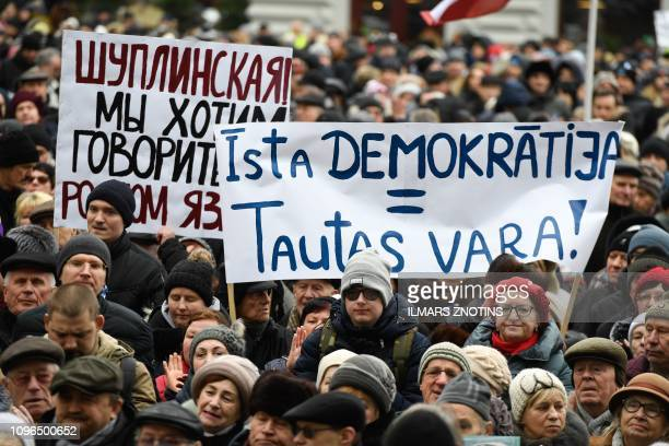 People hold up placards which reads 'Democracy power of people' and 'We want to speak in Russian' at a rally in front of Riga City Hall on February 9...