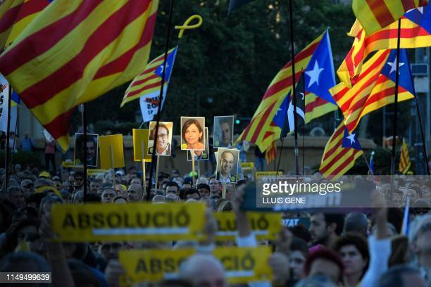 People hold up placards with photos of the Catalan separatist leaders who have been judged in Madrid over their role in Catalonia's failed 2017...