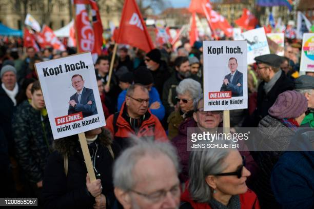 People hold up posters depicting Thuringia's former state premier Bodo Ramelow of the leftwing Die Linke party and reading Keep the head up not the...