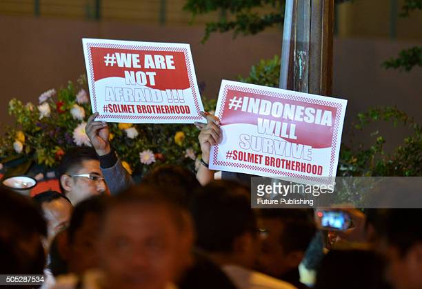 People hold up posters during a citizens' gathering stating 'We are not afraid' near the site of a bomb explosion in front of a shopping mall on...
