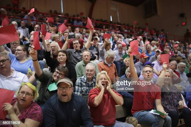 People hold up red pieces of paper to voice disagreement as Congressman Rod Blum speaks to his constituents during a town hall meeting on May 8 2017...