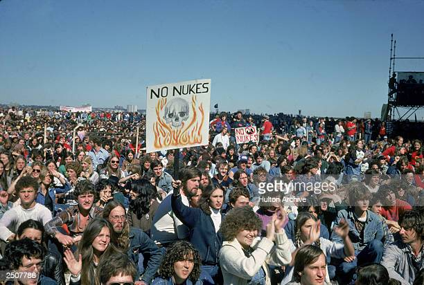 """People hold up signs creading, """"No Nukes,"""" at an anti-nuclear demonstration in New York City, New York, 1982."""